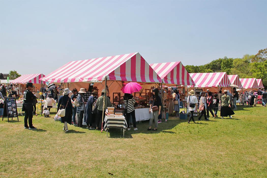 カラフルなテントが並ぶマルシェ会場での買い物の様子