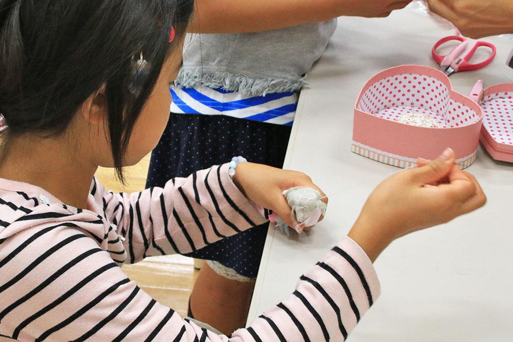 布を縫い、コサージュを作る参加者