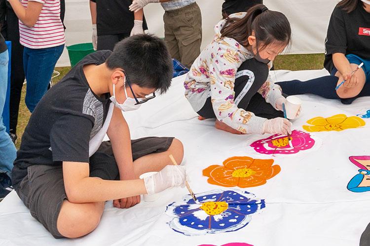ピンクや青の花を描く子供たち
