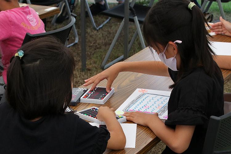 紙にデザインを描く参加の子供