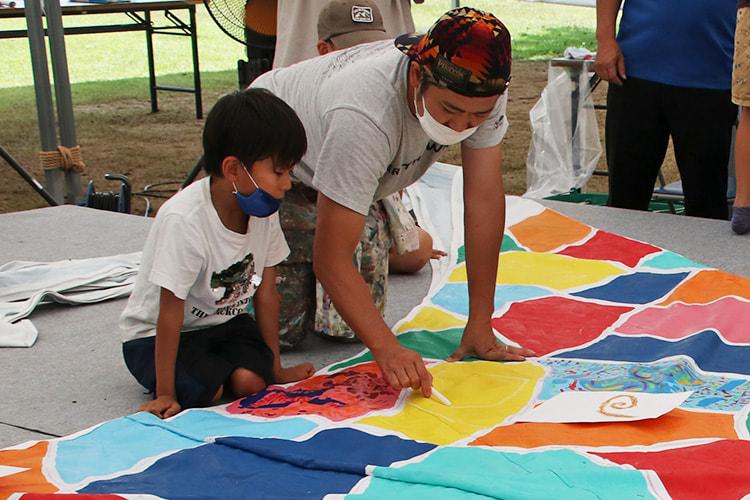 子供に絵をテントに描くアドバイスをするミヤザキさん