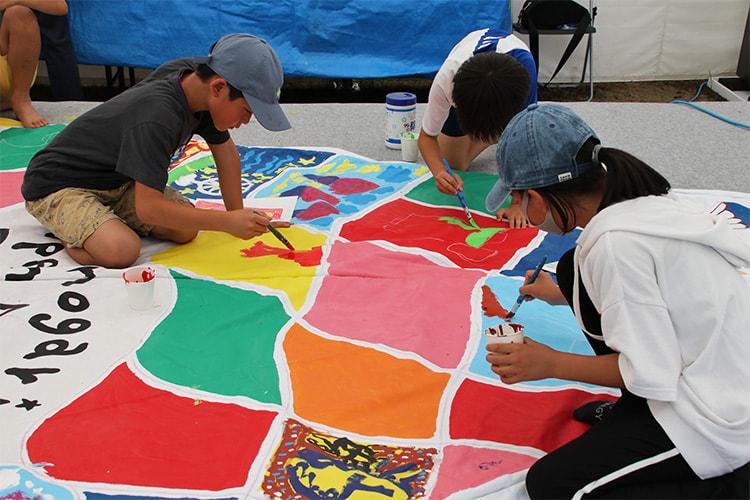 カラフルに色が塗られたテントに絵を描く子供たち
