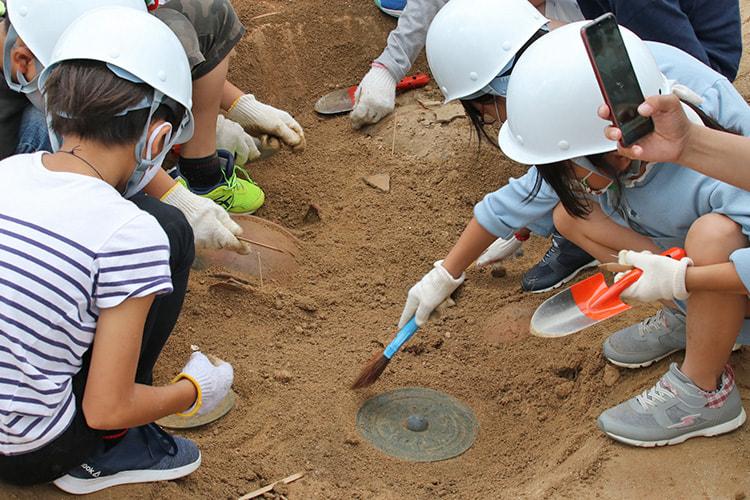 疑似発掘エリアで作業する子供たちにより銅鏡が発掘されている
