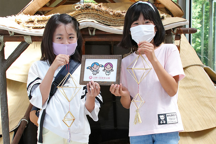 出来上がったヒンメリと公園のマスコットのついたボードを掲げる2人の女の子